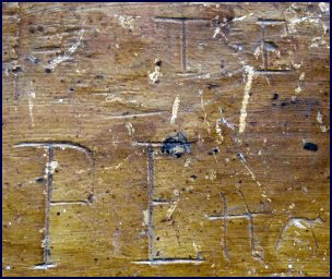 wood and leather bellows detail showing hand-carved initials T.E. and P.E.