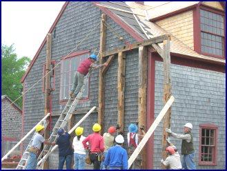 Dan Reagan fits a corner frame onto the larger building frame