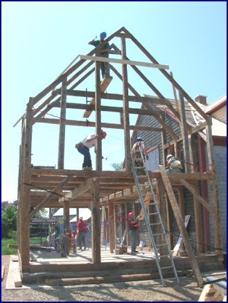 Roof re-construction begins once all four walls have been re-assembled and stabilized