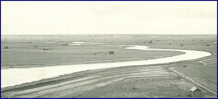 Photograph taken from atop the CBC towers on Cole's Island c.1945. View is looking north along the meander of the Tantramar River. There are upwards of 70 marsh barns in the photograph; also note the covered bridge across Tolars Canal along the extreme right of the photo!