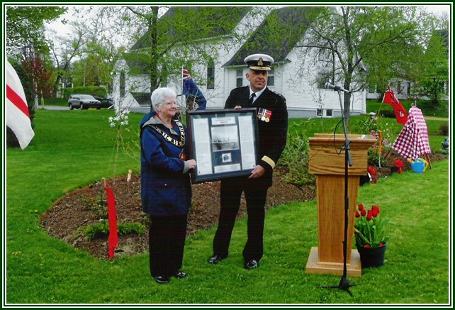 Commodore Andrew Smith presents a framed image of the HMCS Sackville to mayor Pat Estabrooks and the people of the town of Sackville on May 15th, 2010, during the Sackville celebration of the Canadian Navy Centennial. Commodore Smith was born and raised in Sackville, graduating from Tantramar Regional High School in 1979; he has served 31 years in the Navy.