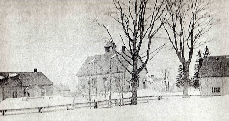 1920 photo of the Job Anderson Blacksmith Shop on its original site.  The shop is the small building to the right of the old school at the centre of photo