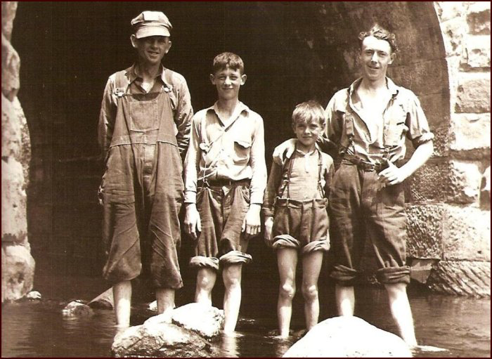 """Left to Right: Edward Read, Freddie Read, Stanley (Buddy) Ward (1932–1952) and Jesse MacKinnon (Stanley's uncle) at the """"deep hole"""" under the CNR line in Frosty Hollow c.1942. Stanley's mother died when he was just six years old so he was brought up by his MacKinnon grandparents in Frosty Hollow (Photo by Charles C.E. McKinnon). (C. MacKinnon collection)"""