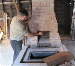 Paul Fontaine fits out the chimney opening with a steel hood, and the work table with a water trough (to wet the coal).