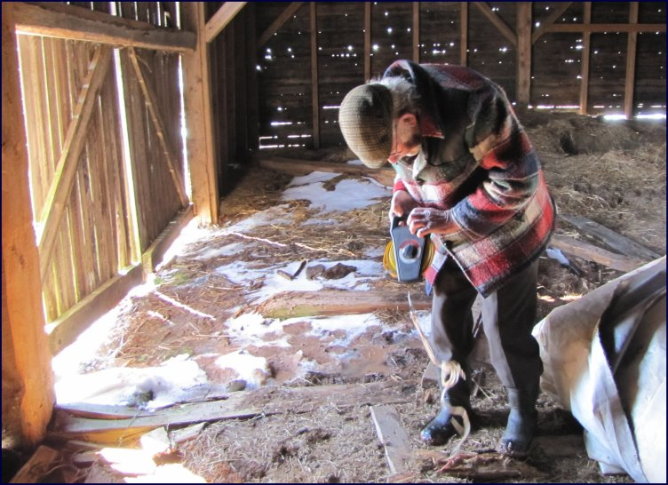 Daniel doing measurements at the Scoggins barn prior to its reconstruction