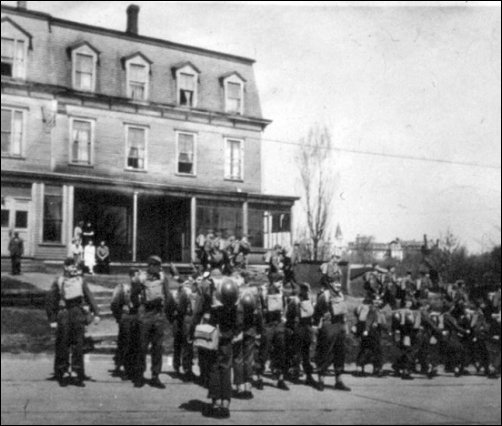 "Local cadets lined up in front of ""The Barn"". This photo is from the era when Brunswick House was used by Mount Allison (seen in the distant background) and re-named Allison Hall (circa 1941)."