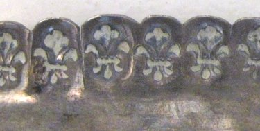 Bottom view of plate rim with the stamp (each fleur-de-lis about 0.46 x 0.60 cm)